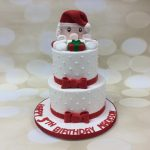 two tier cake with swiss dots and Santa on top for child's birthday
